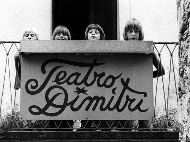 Schwarzweiss-Fotografie: Vier Kinder strecken ihre Köpfe hinter einem Schild hervor, auf dem «Teatro Dimitri» steht.