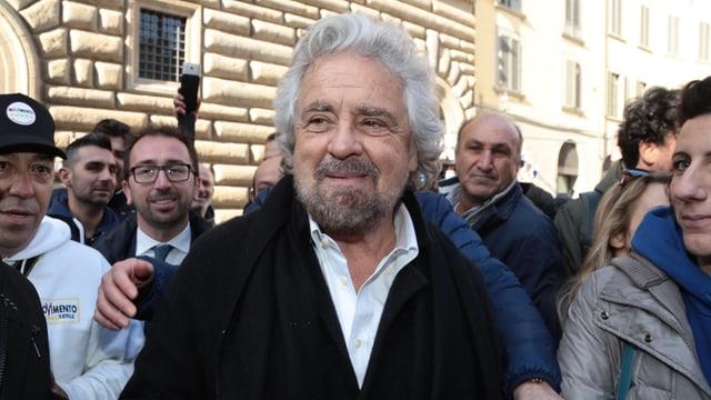 Der weisshaarige Grillo umgeben von Männern, er lächelt.