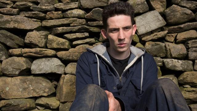 Ein junger Mann sitzt nachdenklich vor einer Steinmauer.
