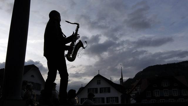 Ein Mann mit Saxophon vor leicht bewölktem Abendhimmel und den Häusern von Stans