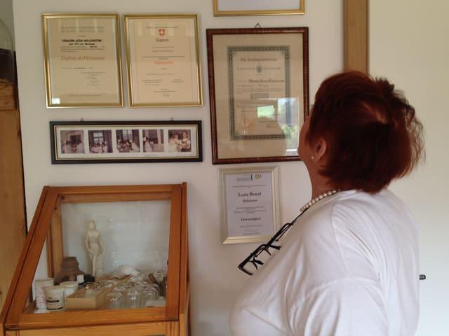 Brand betrachtet ihre Diplome an der Wand.