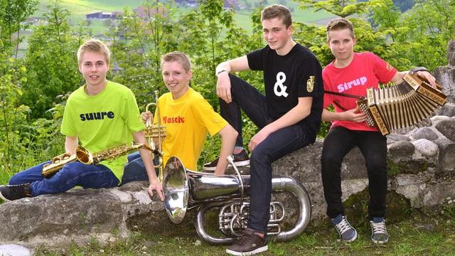 Vier junge Musikanten auf einer Mauer.