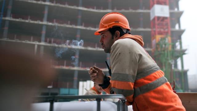 Ein Mann raucht auf einer Baustelle.