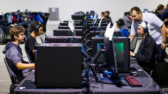 Junge Menschen sitzen an vielen Computern.