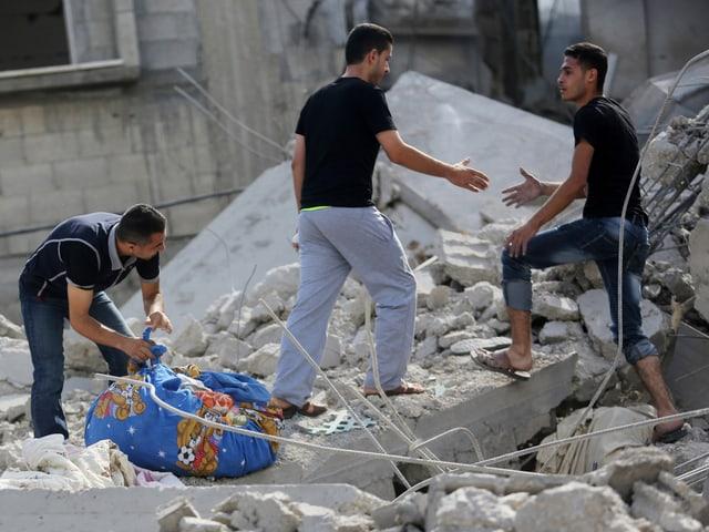 Drei junge Männer stehen in Trümmern.