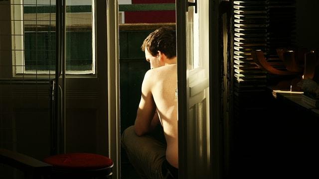 Ein Mann sitzt auf einem Balkon. Sie Sonne scheint auf seinen nakten Oberkörper.