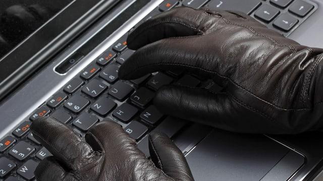 Blick auf eine Tastatur mit behandschuhten Händen