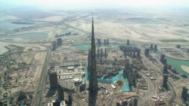Eine Luftaufnahme zeigt den Burj Khalifa neben vielen kleinen Häusern in Dubai.