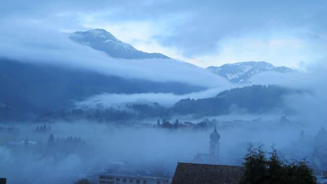 Blick über Disentis mit einem aus dem Nebel ragenden Kirchturm, dahinter teilweise schneebedeckte Berge.
