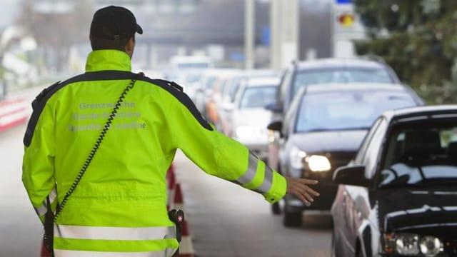 Ein Grenzwächter in einer gelben Jacke winkt eine Autokolonne durch