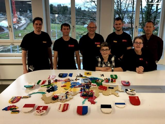 Das Team steht hinter dem Tisch mit der Lego-Schweiz