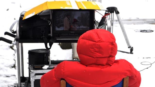 Ein roter Mann sitzt in einem blauen Stuhl, vor sich ein Bildschirm, dahinter Schneelandschaft.