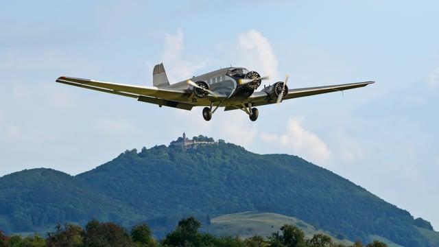 Oldtimer-Flugzeug Ju52 fliegt über Jura Landschaft