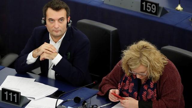 Zwei Personen auf einer Parlamentsbank.