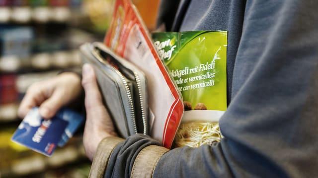 Frau mit Einkäufen unter dem Arm und der Cumuluskarte in der Hand