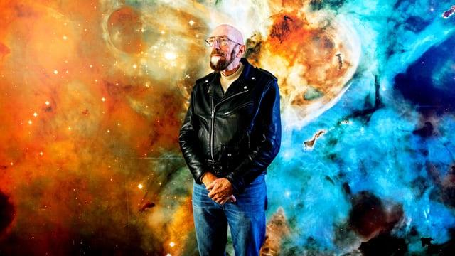 Kip Thorne vor einer Wand mit Kosmos-Muster.