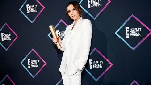 Victoria Beckham im weissen Anzug posiert mit ihrem Preis.