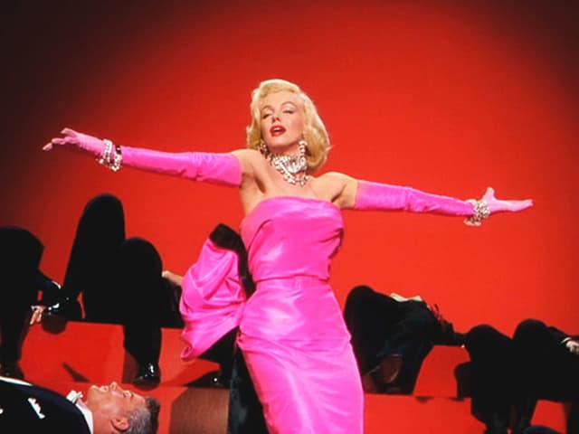 Marilyn Monroe in pinkfarbenem Kleid vor rotem Hintergrund.