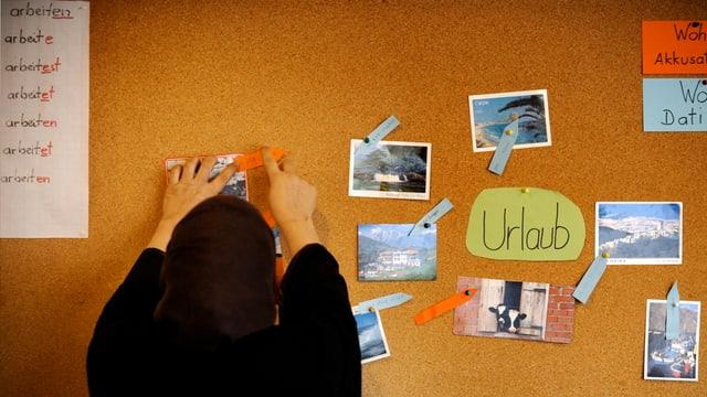 Eine Frau mit Kopftuch hängt eine Notiz an die Wand.