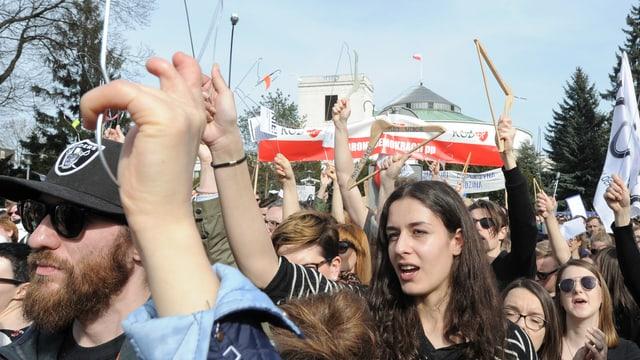 Demonstranten halten Kleiderbügel hoch