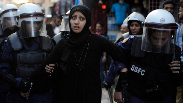 Vier Polizisten führen eine junge Frau ab.