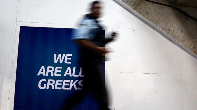 """Ein Mann geht an einem Schild vorbei, auf dem steht """"we are all greeks"""", """"wir sind alle Griechen""""."""