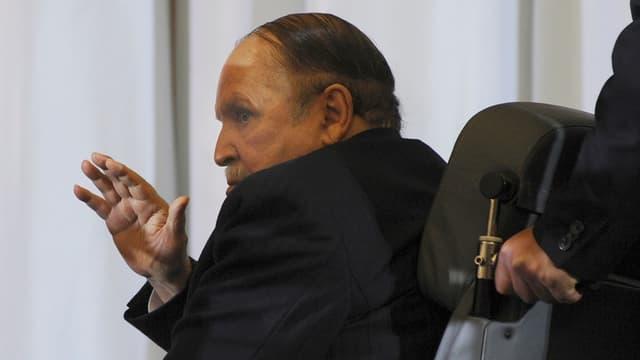 Ein alter Mann sitzt auf einem Stuhl, halb abgewandt und hebt die Hand.