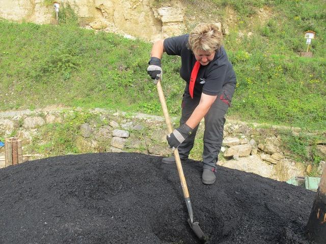 Frau auf schwarzem Kohleberg.