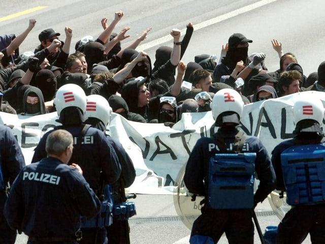 Der «Schwarze Block» 2005 in Zürich, davor Polizisten in Vollmontur.