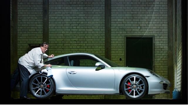 Ein Mann putzt einen Porsche auf der Bühne.