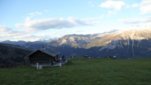 Hütte vor Bergkette im Sonnenuntergang.