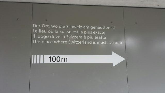 graue Wand mit Aufschrift: Der Ort, wo die Schweiz am Genauesten ist.