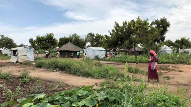 Frau geht über Boden, Gemüsegarten im Vordergrund, Hütten im Hintergrund.