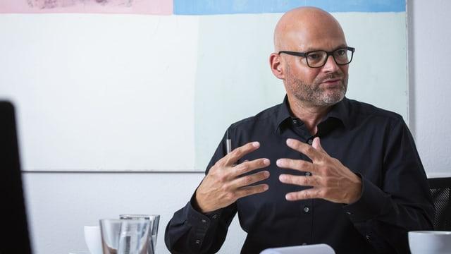 Ein Mann mit Brille spricht und gestikuliert vor einem pastellfarbenen Gemälde.