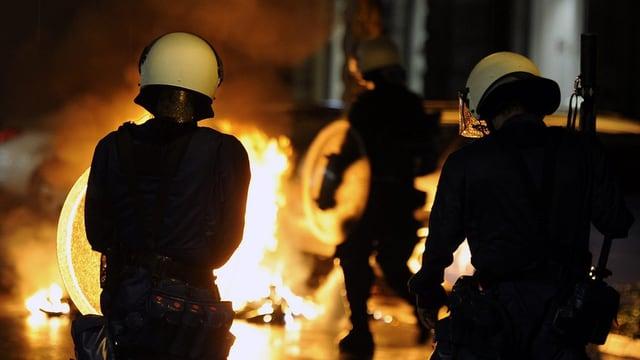 Polizisten von hinten, vor ihnen brennt es