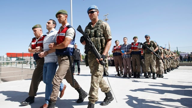 Türkische Soldaten führen die Angeklagten in Reih und Glied zum Gericht.