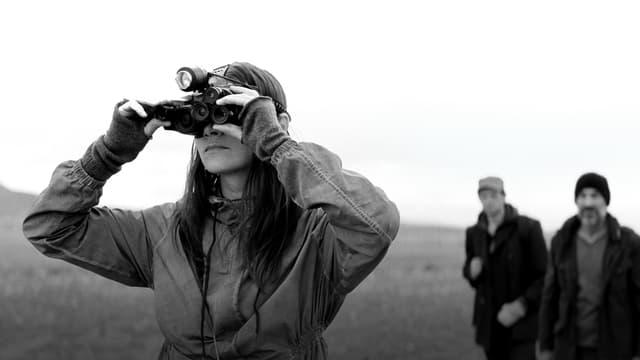 Eine Frau steht im Vordergrund und schaut durch ein Fernrohr. Im Hintergrund stehen zwei Männer.