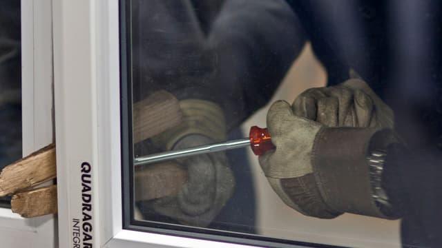 Zwei Hände mit Handschuhen versuchen mit Holzstücken und einem Schraubenzieher ein Fenster aufzubrechen.