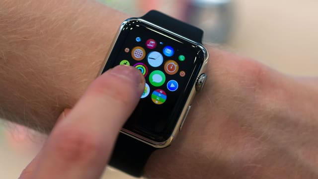 Ein Zeigefinger drückt auf ein Symbol auf einer Apple Watch.