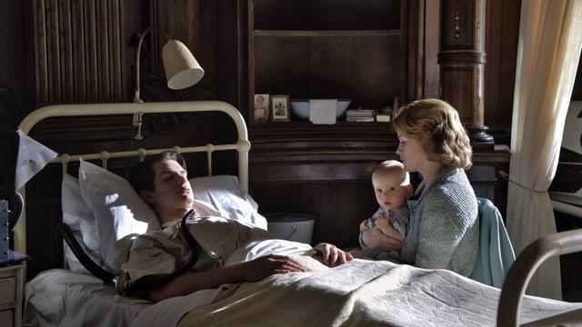 Ein Mann liegt im Bett und seine Frau und sein Kind sitzen daneben.
