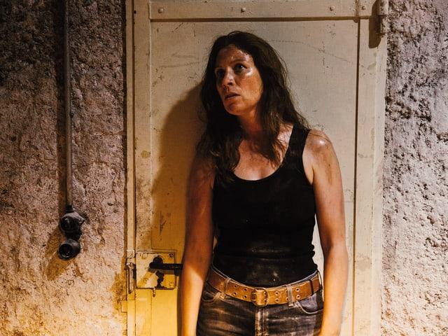 Anna-Maria steht in einem Keller. Sie sieht müde aus, ist schmutzig und verschwitzt.