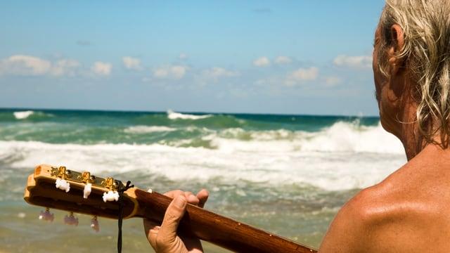 Mann mit Gitarre spielt am Meeresstrand.