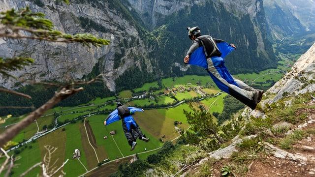 Zwei Männer in Flügel-Anzügen stürzen sich von einem Berg in die Tiefe.