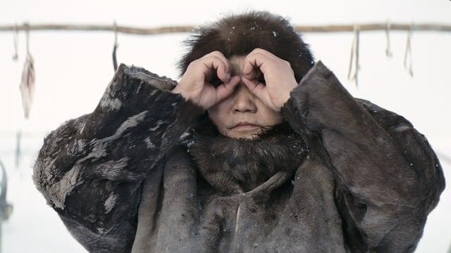 Eine Iniut-Frau blickt durch ihre Finger wie durch ein Fernrohr.