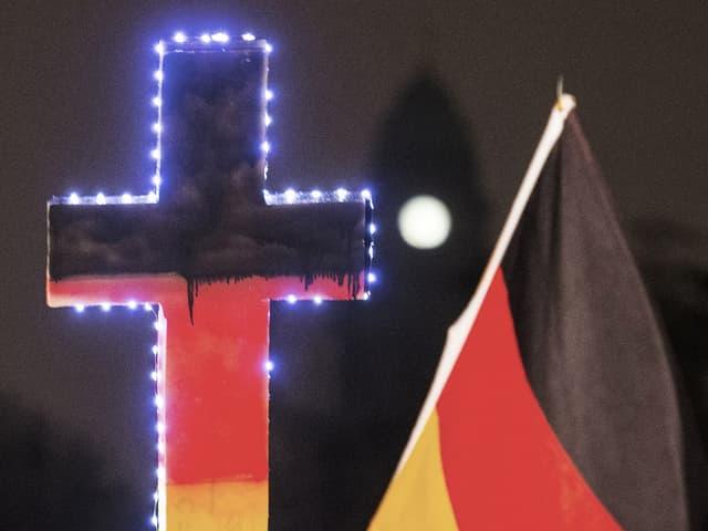 Ein Kreuz in den deutschen Nationalfarben und eine Landesfahne