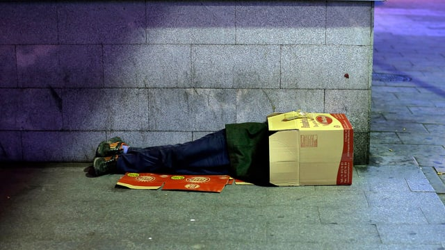 Ein Obdachloser schläft mit dem Kopf in einer Kartonschachtel.
