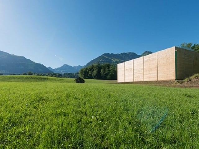 Ein Holzkubus auf einer satten, grünen Wiese. Im Hintergrund berge und blauer Himmel.