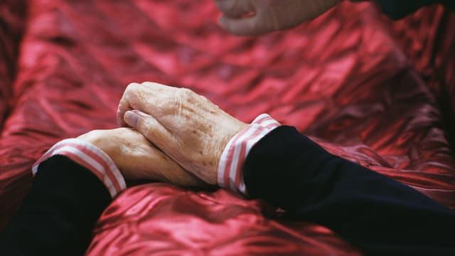 Zwei Hände auf einer roten Decke. Es sind die Hände einer Toten.