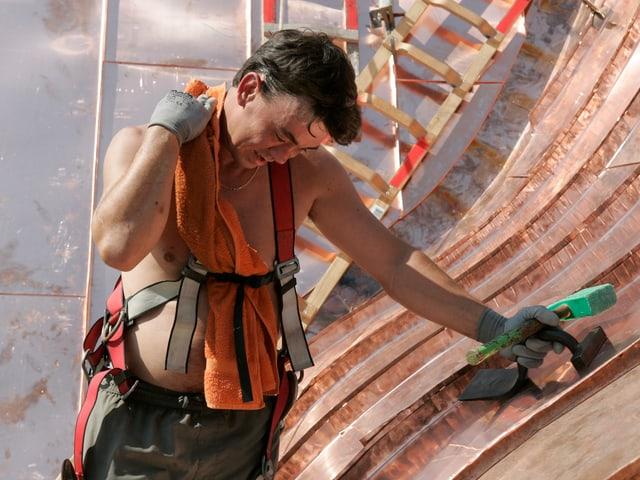 Ein Bauarbeiter auf einem Metalldach hat ein Tuch um den Hals gelegt. Er schwitzt stark.