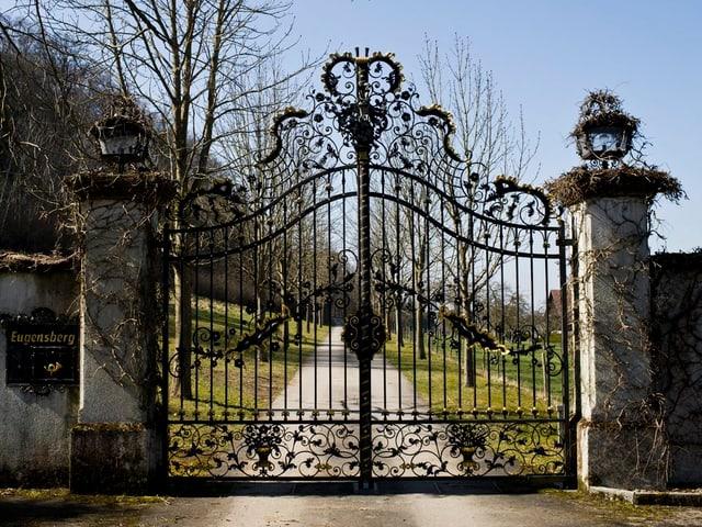 Ein grosses Tor aus Schmiedeisen - dahinter der Park, der das SChloss Eugensberg umgibt.